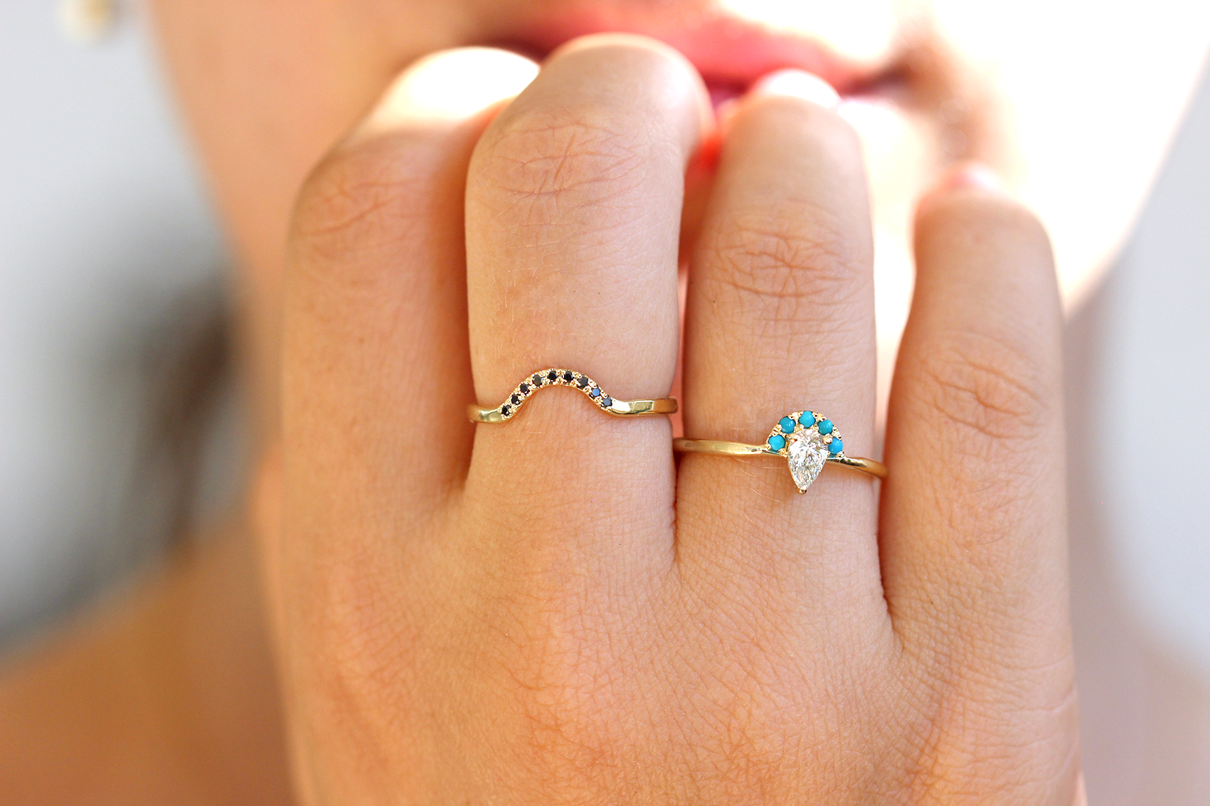pear cut diamond ring crowned with bright turquoises gemstones on hand