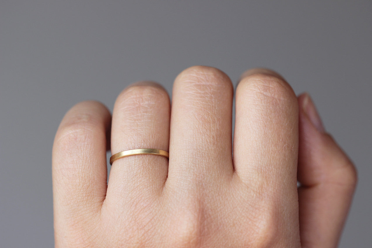 simple wedding ring on hand