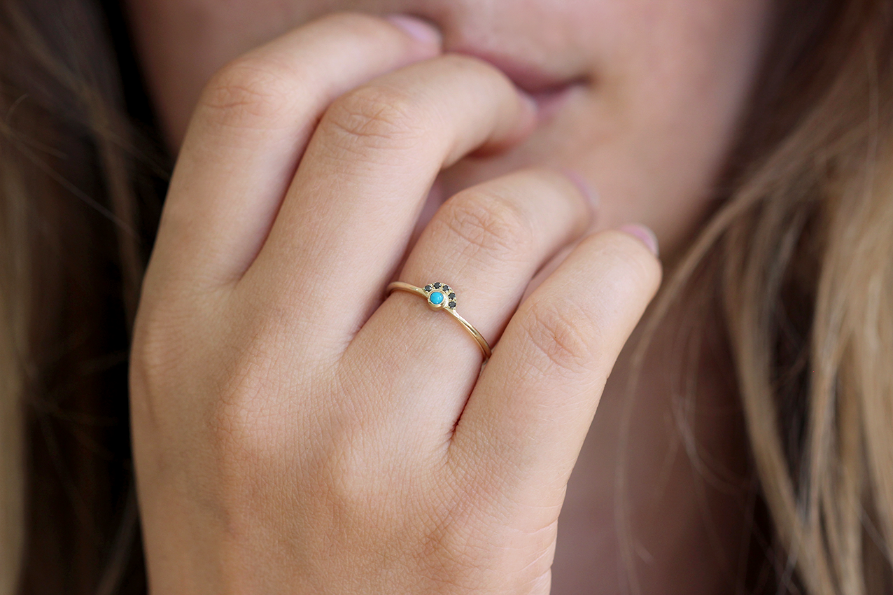 Little and delicate turquoise ring on finger
