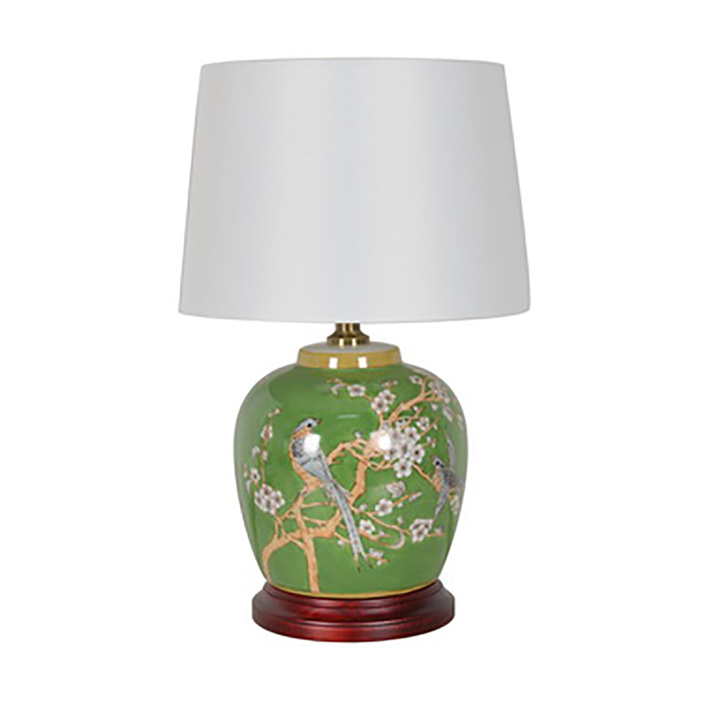 green bird motif lamp with wooden base and white empire cylinder shade