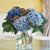 Artificial blue hydrangeas in glass vase