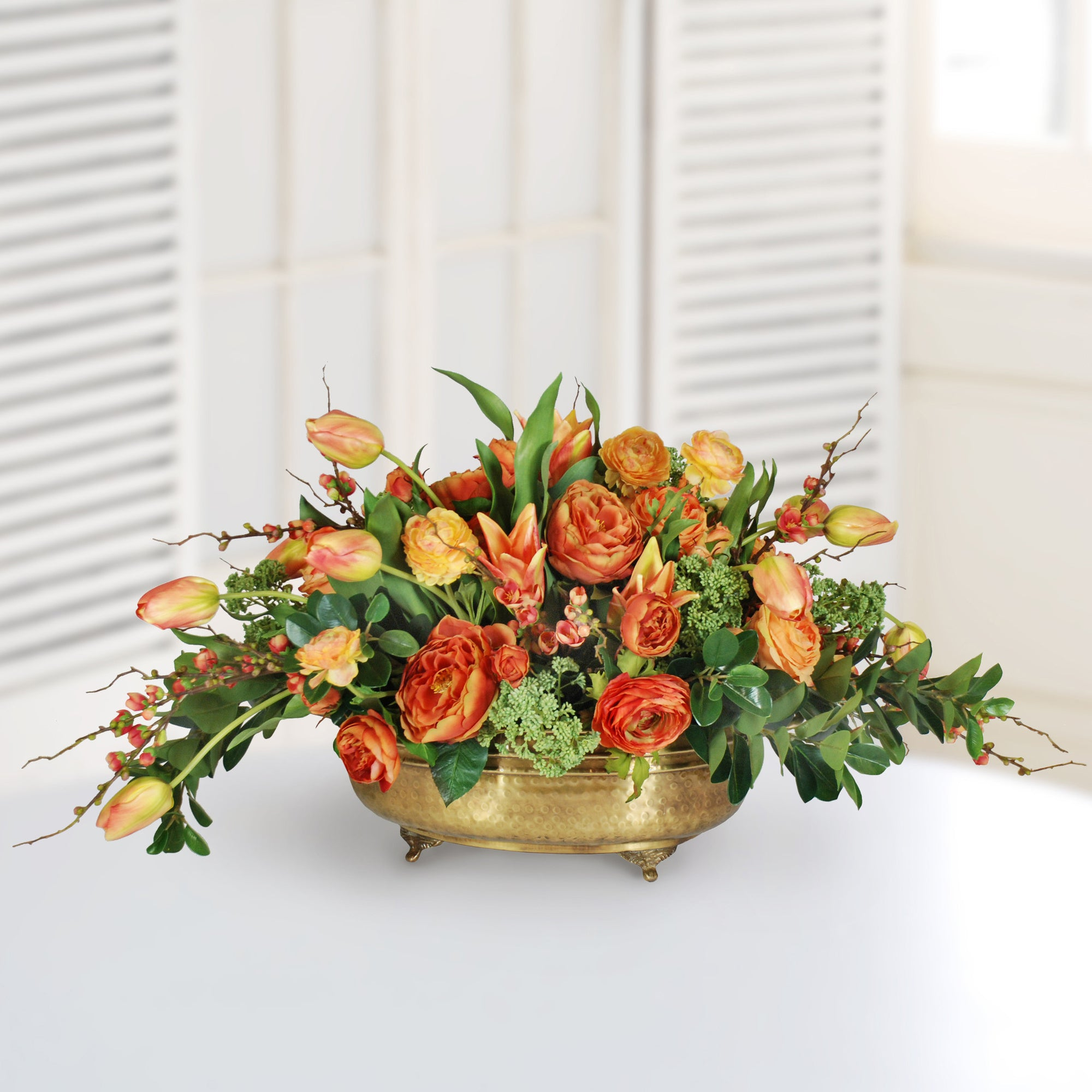 Mixed orange tulip and ranunculus in brass planter