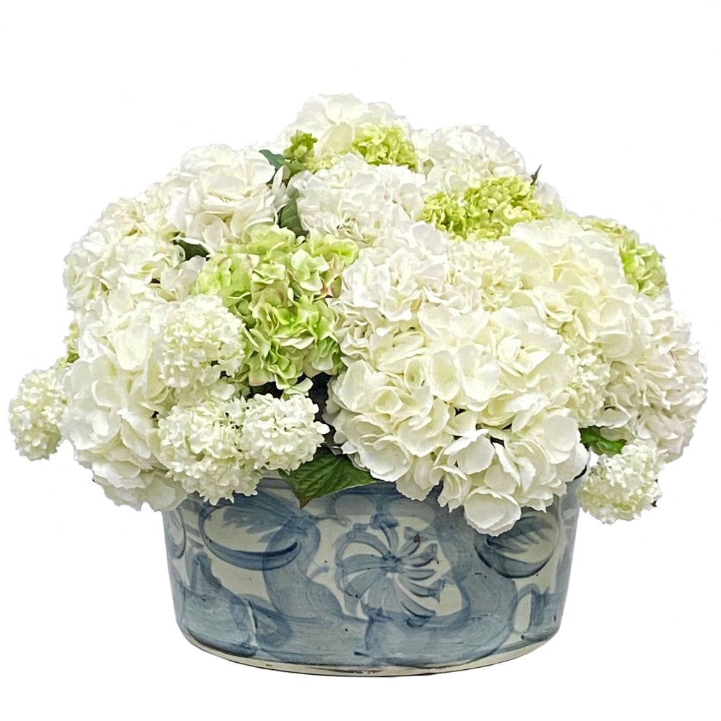 Mixed white and light green hydrangeas in white and light blue ceramic pot