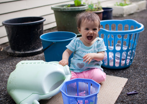 Photo of a smiling baby sitting on a mat outside