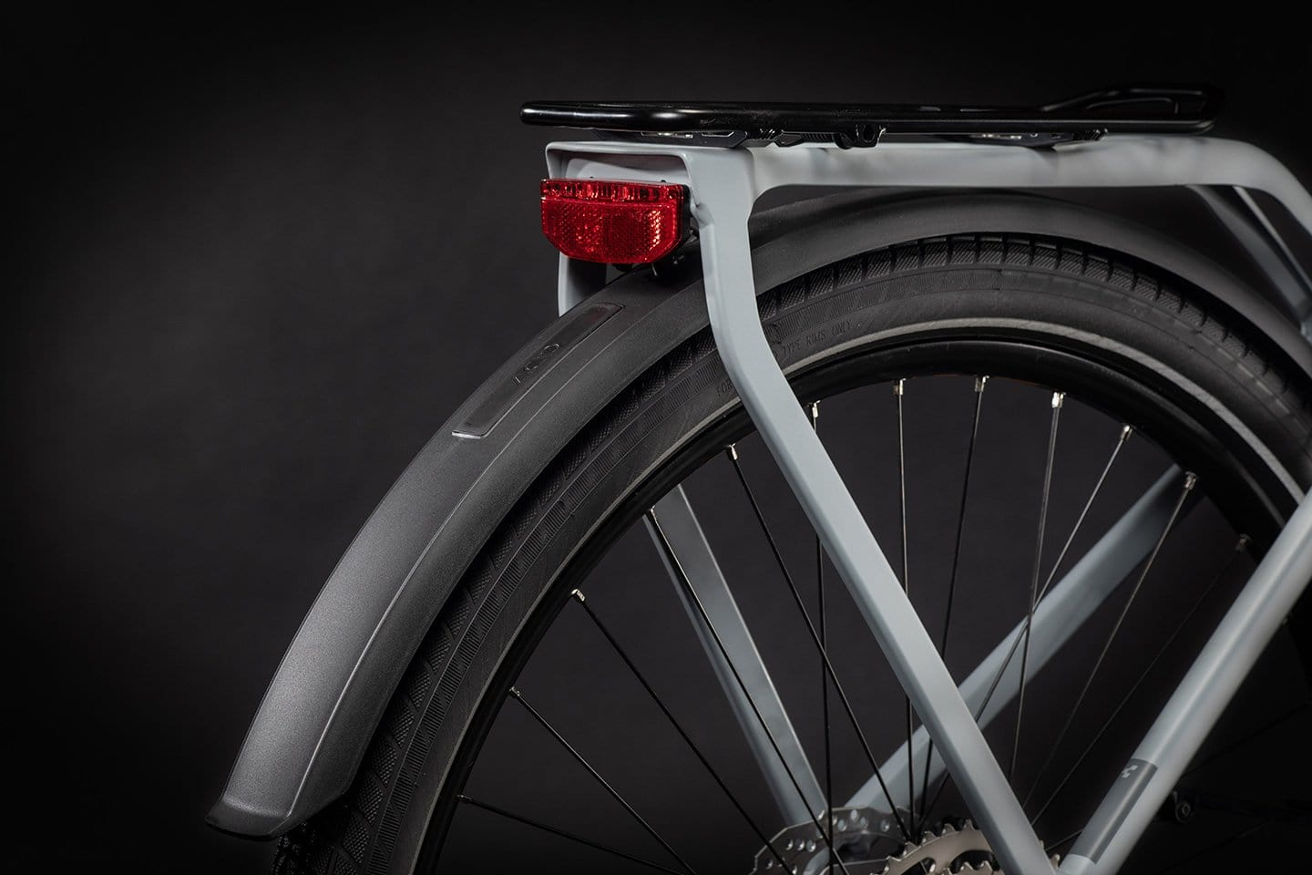 Close-up of rear wheel with rack, fender, and light. Disc brakes.