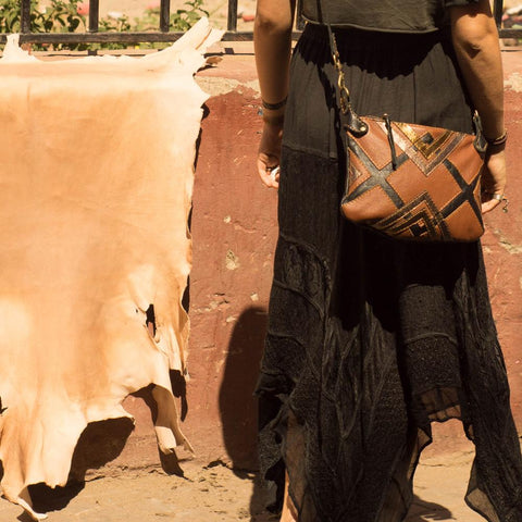 Girl standing next to Moroccan leather drying in sun