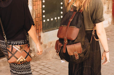 two ladies wearing leather bags