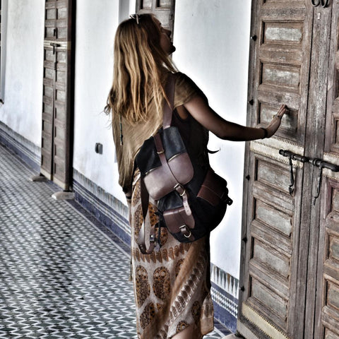 Girl wearing leather backpack while looking at a door