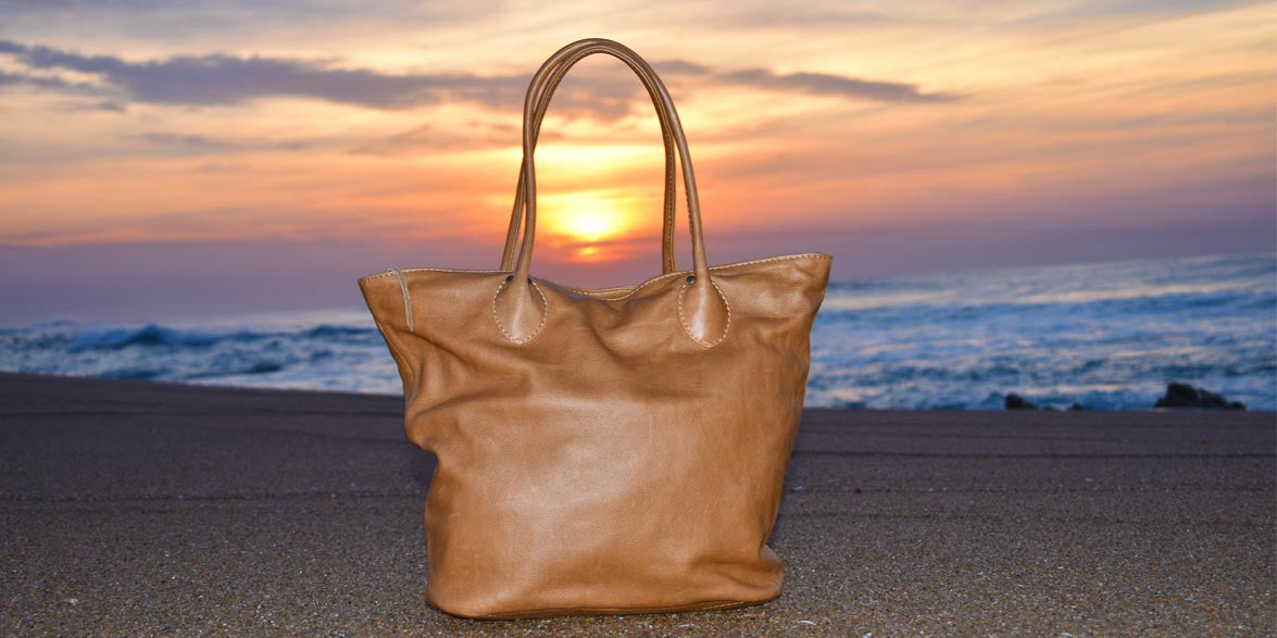Leather tote bag on beach with sunrise