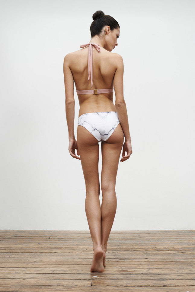 halterneck bikini top and low-rise bikini bottoms, reversible in a white marble print, back view on model