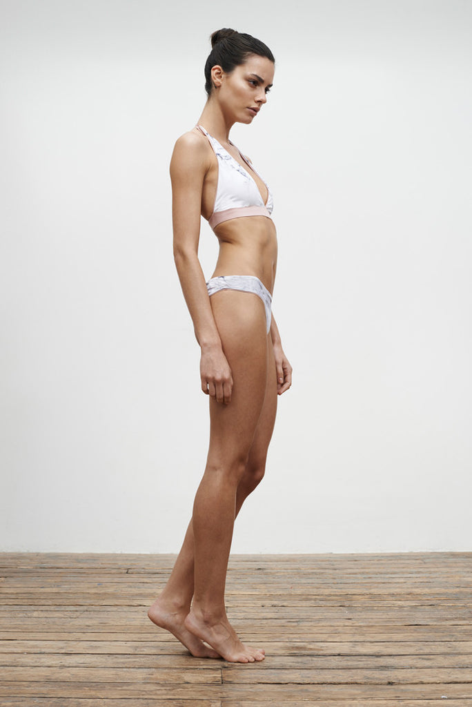 halterneck bikini top and low-rise bikini bottoms, reversible in a white marble print, side view on model