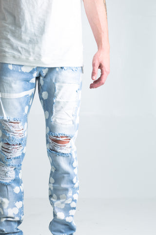 "Dropped Ripped Denim (Stone Wash) | Bleached light blue stone washed denim Distressed knee rips White paint stripe across right thigh White spot details throughout 2 front zipper pockets 100% cotton Skinny fit 34"" standard inseam"