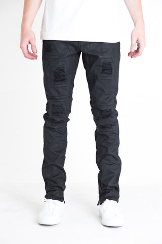 "Elan Ripped Denim | Black waxed denim Wax effect Distressed with patchwork detailing Extended side zipper pocket Inner ankle zippers 100% cotton Skinny fit 34"" standard inseam"
