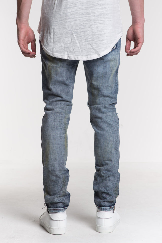 "Tempest Ripped Denim | Medium blue denim Lightly distressed with allover patchwork on front Rustic grey effect 100% cotton Skinny fit 34"" standard inseam"