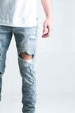 "Rita Ripped Denim | Light blue denim Destroyed rips Subtle whisker dye effects Patchwork details and paint splatter 2 front zipper pockets 100% cotton Skinny fit 34"" standard inseam"