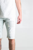 "Light blue stone washed denim shorts Unexposed distressing with ribbing details underneath 2 front zipper pockets 100% cotton Skinny fit 12.5"" inseam"