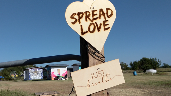 "PLUR at Quasar Festival in Texas: ""Just Breathe"" message and heart-shaped sign with ""Spread Love"""