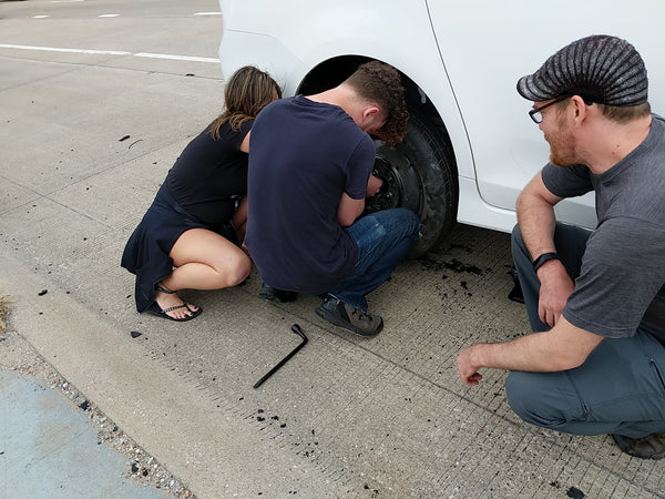 Post-festival excitement during our road trip: Sam and Dana attach a spare tire while Jon supervises