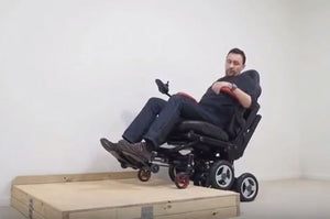 Wheelchair uses a single actuator to get up a step
