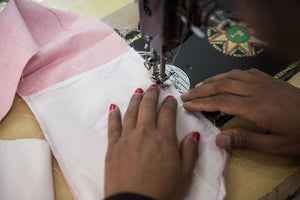 fair trade clothing maker sewing pink and white cotton together