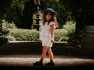 little girl wearing a vintage lacy blouse and shorts and hat