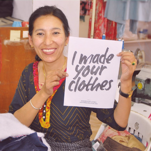 smiling woman holding I made your clothes sign