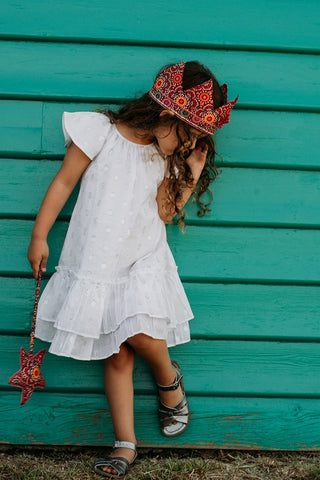 little girl wearing a white frill dress with silver dots and trim