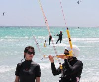 A woman getting her first kite surfing lesson