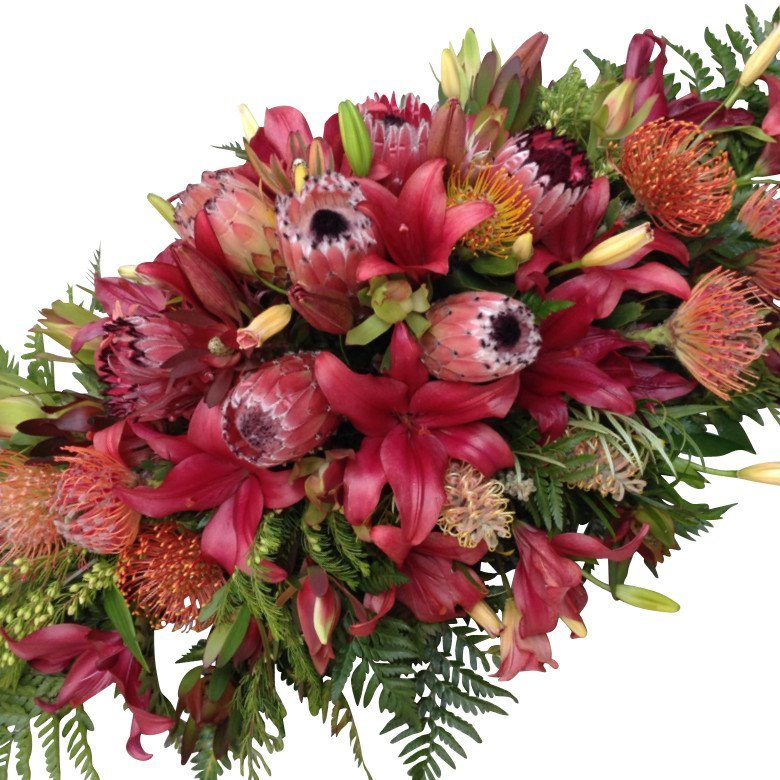 Coffin or Casket Spray Funeral Flowers in Red seasonal mix