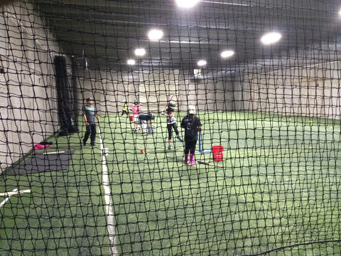 Team working in large room on fielding and hitting