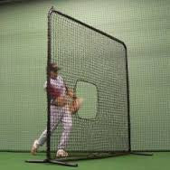 Softball pitcher using softball pitching screen indoors
