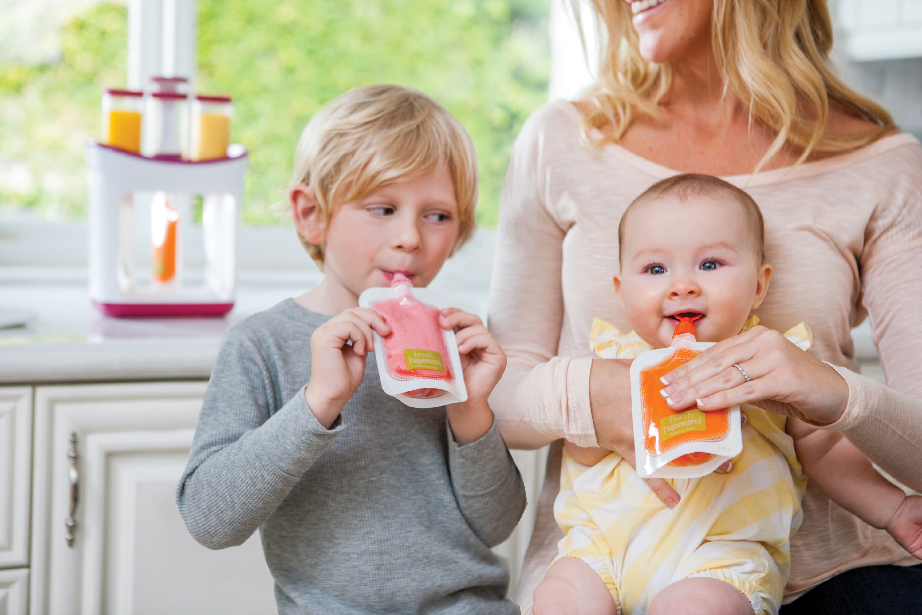A baby and a toddler enjoy fresh Infantino Squeeze pouches