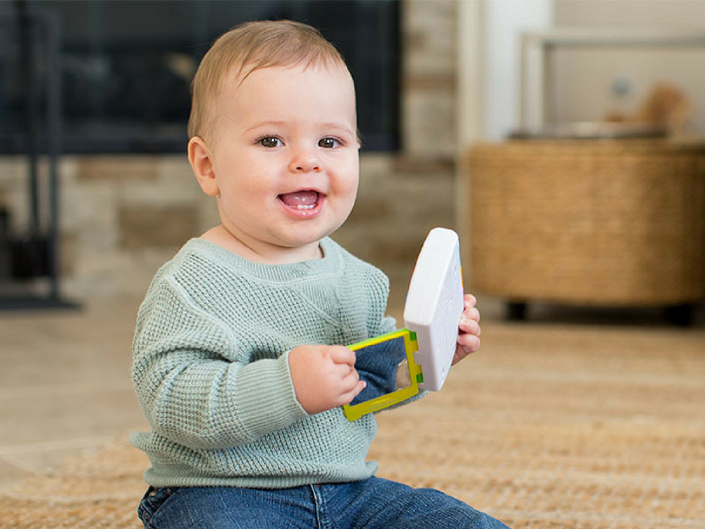A happy baby plays with an interactive Infantino toy phone