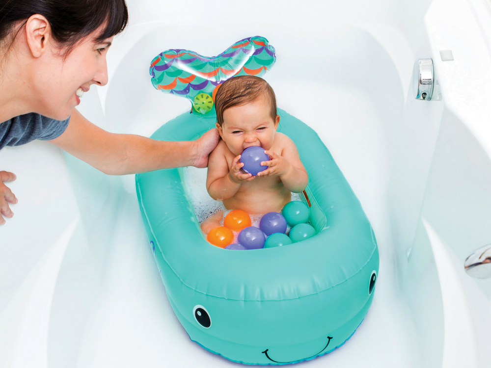A happy baby takes a bath in his Infantino inflatable whale shaped tub