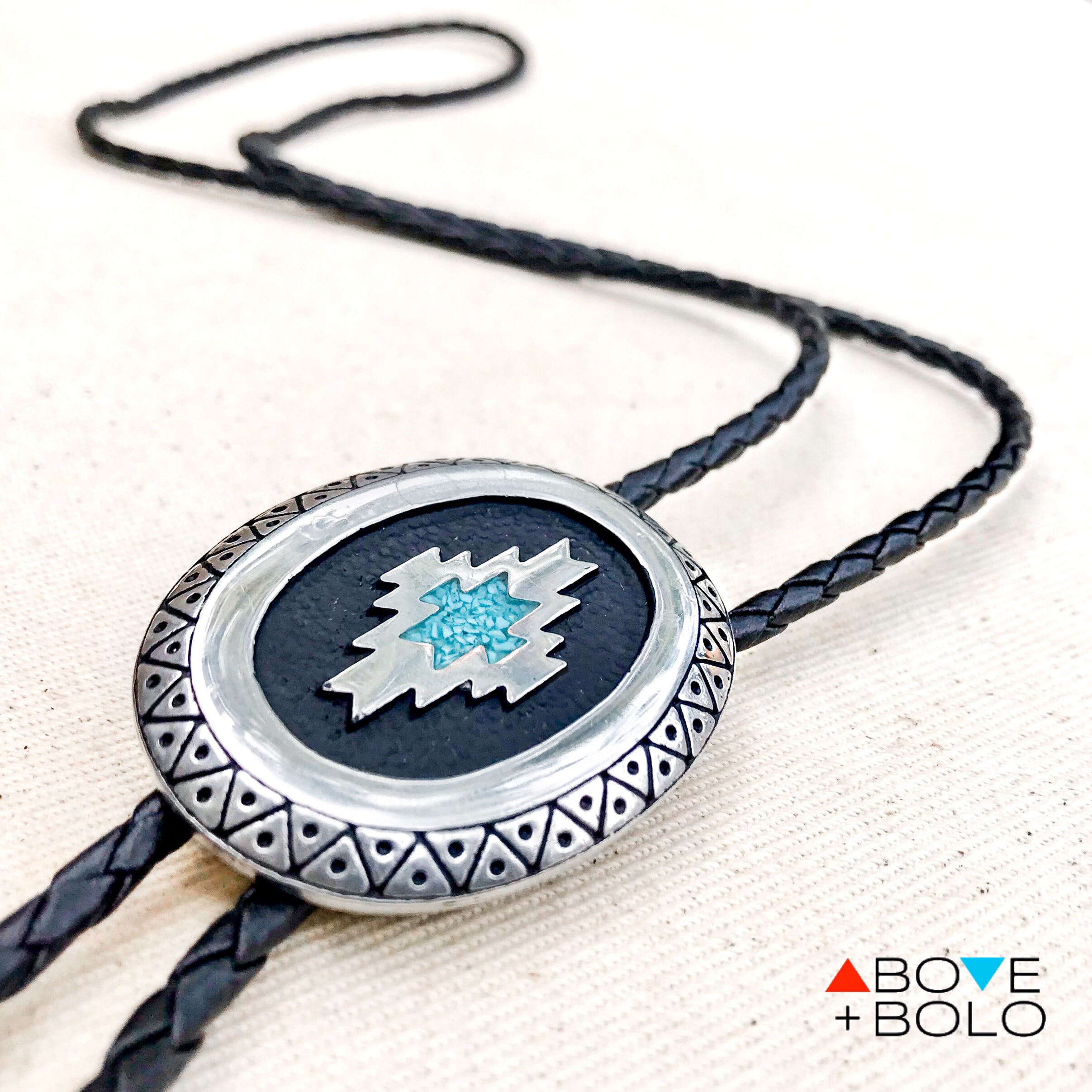 f3ac207e50db ... angled photo of turquoise chip inlay bolo tie with an oval pendant and geometric  design ...