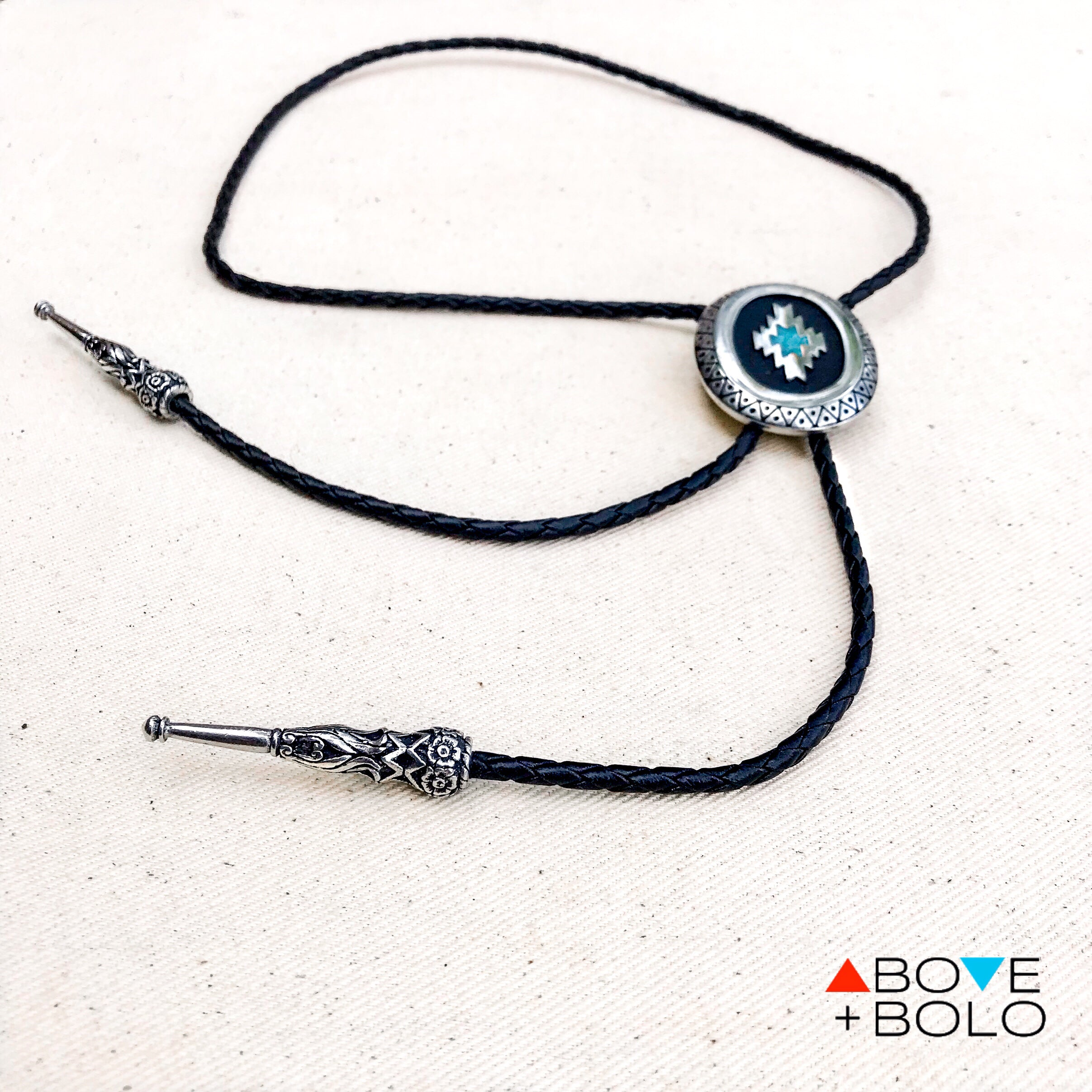 03172200128e ... photo of turquoise chip inlay bolo tie with an oval pendant and · turquoise  chip inlay bolo tie with an oval pendant and geometric design close up ...