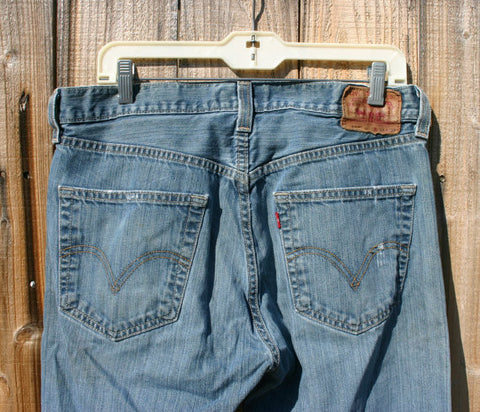 A Fantastic Pair of Levis 501s W/ Leather Back Patch Great Distressed Finish Size 34/32 Holes Near Bottom Of One Leg Whiskering Ready To Go!