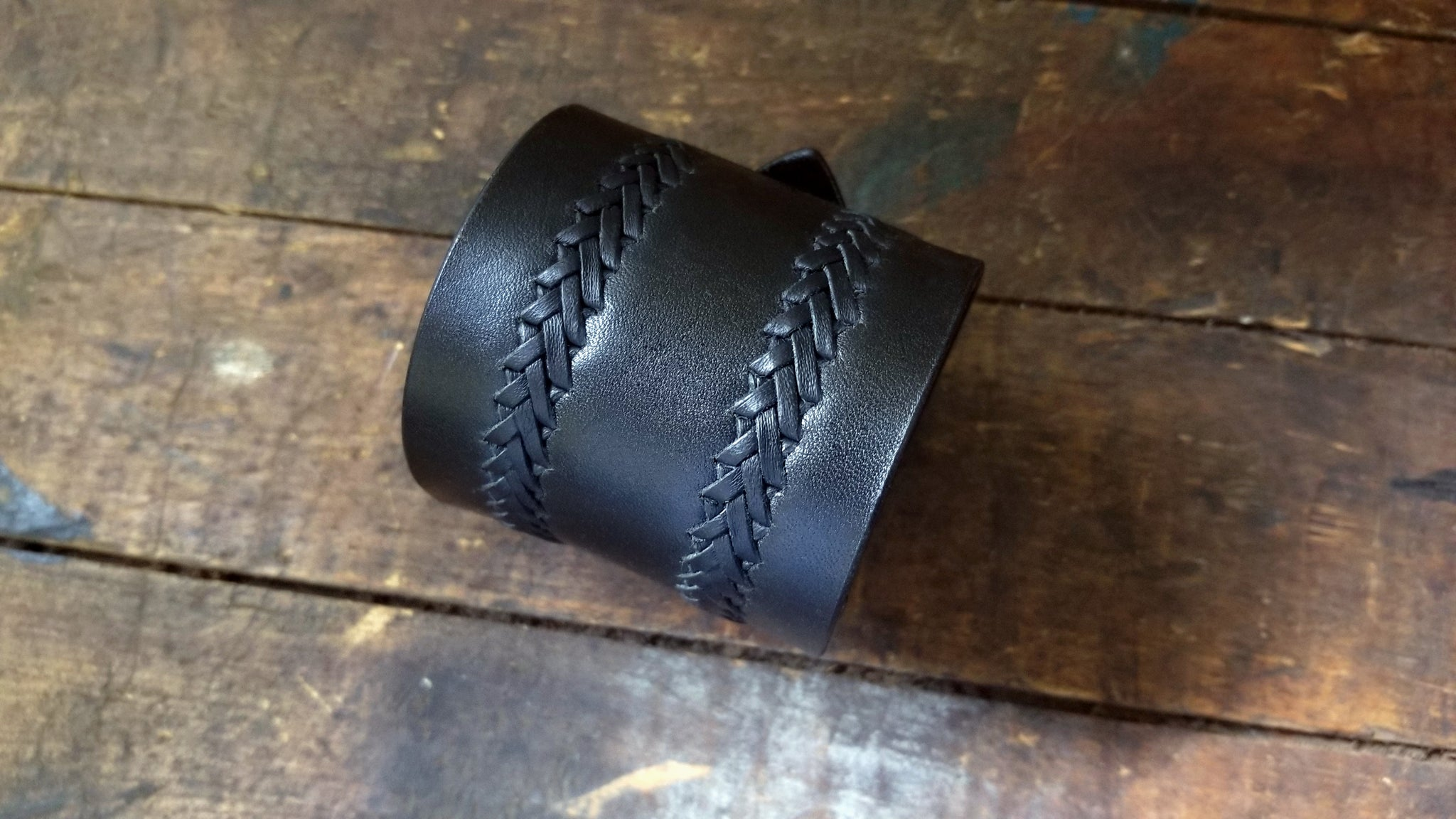 2 rows of a ladder stitch hand lacing detail on Aga, Men's Wide Buckle Leather Cuff, in black