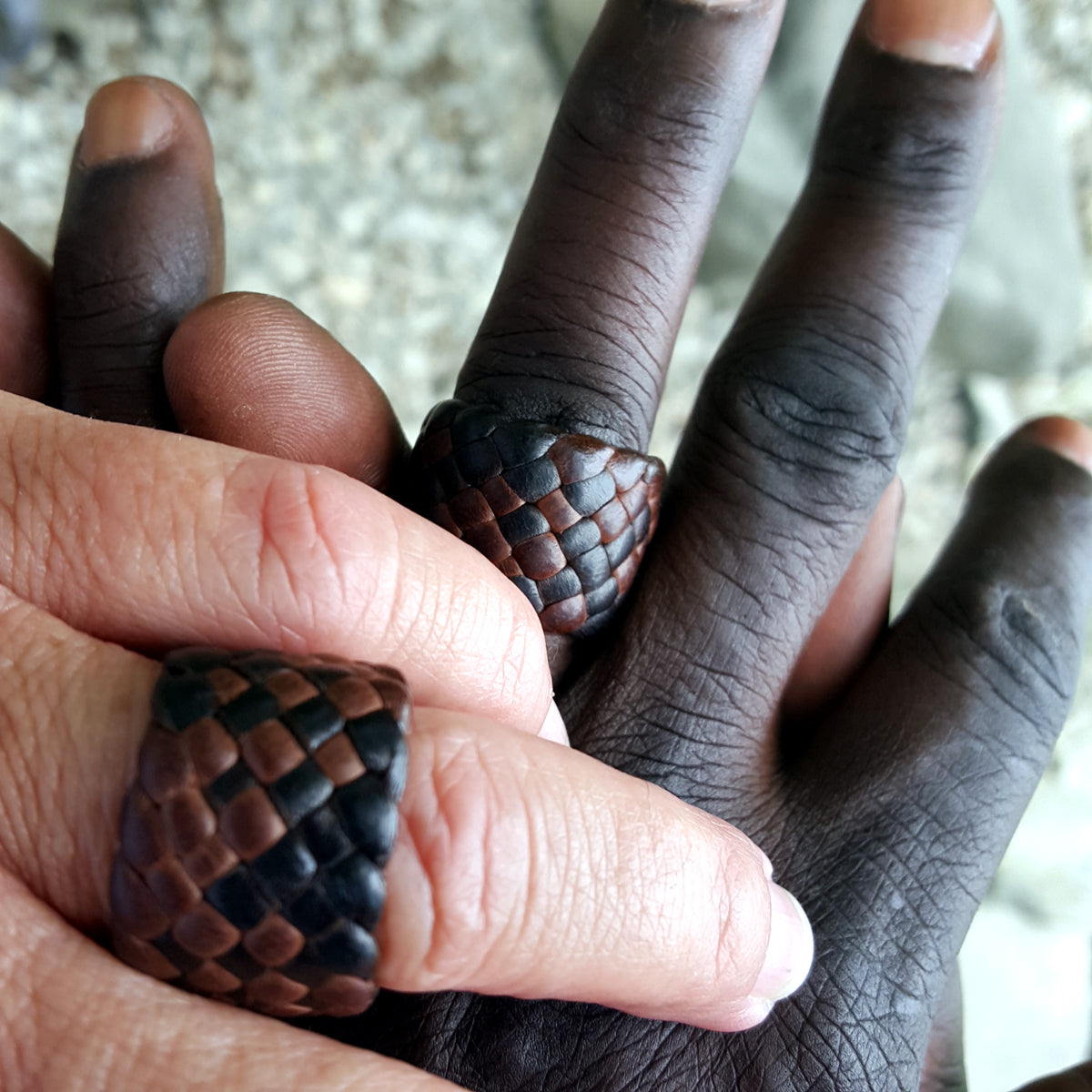 "chocolate and mahogany kama braided leather rings, 3/4"" and 5/8"" (custom size) on male and female models"