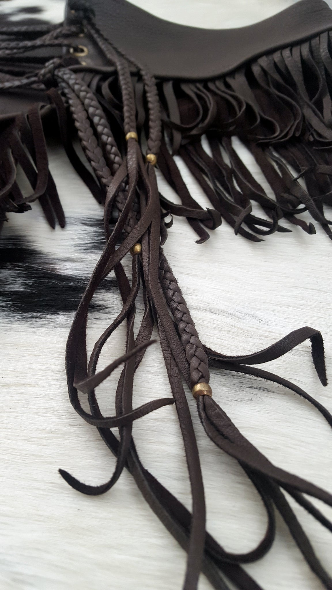 close up image of deerskin leather booty shorts, booty shorts braided laced ties and fringe