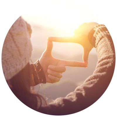 Lady making camera shape with fingers into sunset