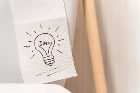 Toilet paper with lightbulb and idea drawn on sheet