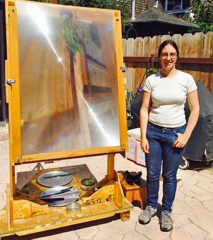 Tawny Reynolds next to the giant magnifying glass she uses to focus sunshine and create Sundrop Jewelry