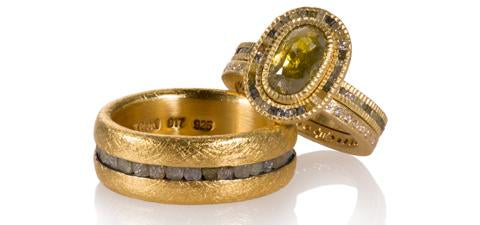 Three yellow gold rings. One greenish oval diamond with raw cubes surrounting it and down the shank. It is with a band with white diamonds. They are both sitting on a 22k gold band with raw cube diamonds in the center