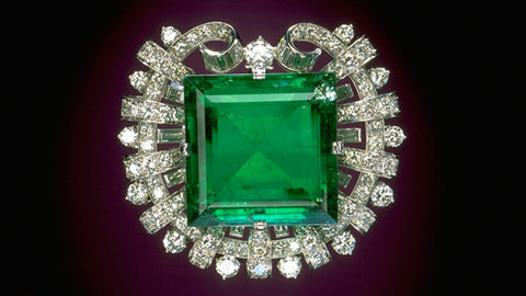 Large emerald square brooch with diamond surrounding it.