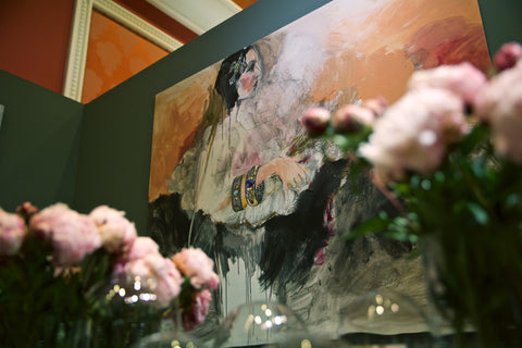 Painting on the wall of the Arman booth with flowers in front