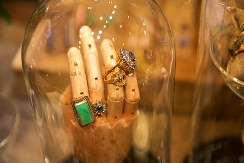 Arman rings displayed on wooden hand under glass bulb