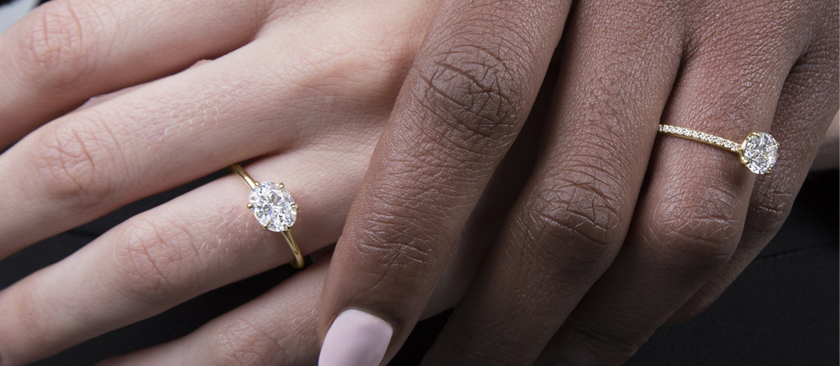 Two feminine hands (one with lighter skin) both have engagement rings on their wedding fingers. One ring is a round diamond with pave setting and the other is an oval diamond set east west in a yellow gold simple setting