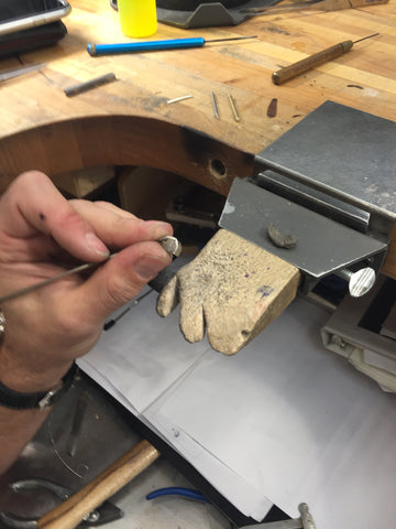 Close up of jewelry bench at todd reed of an artist creating a bezel for a diamond