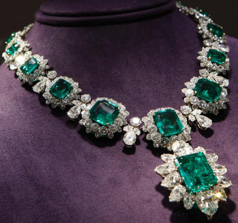 Large emerald and diamond estate necklace on purple neck form.